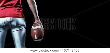 Mid section of sportsman with American football against black
