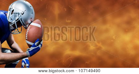 Close-up of upset American football player with ball against orange background