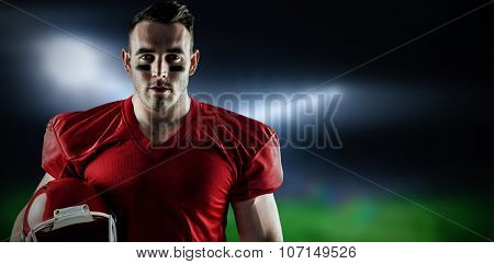 American football player looking at camera against football pitch under bright lights