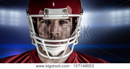American football player looking at camera against spotlights