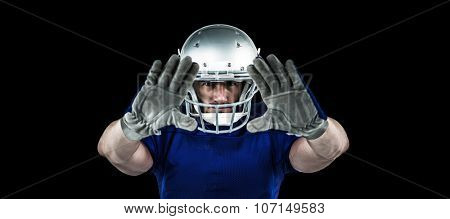 Portrait American football player defending against black