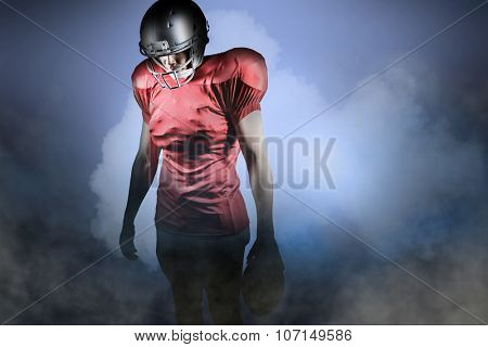 American football player looking down while standing against cloudy sky