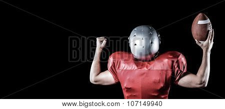 Rear view of American football player cheering while holding ball against black