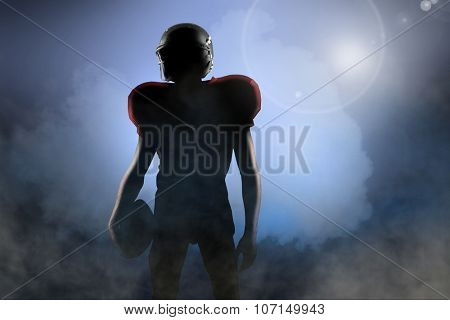 American football player in red jersey looking away against cloudy sky