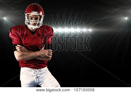 Portrait of serious american football player with arms crossed against spotlight