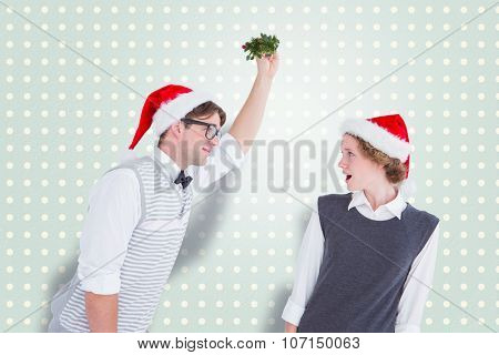 Geeky hipster holding mistletoe against blue and cream patterned wallpaper