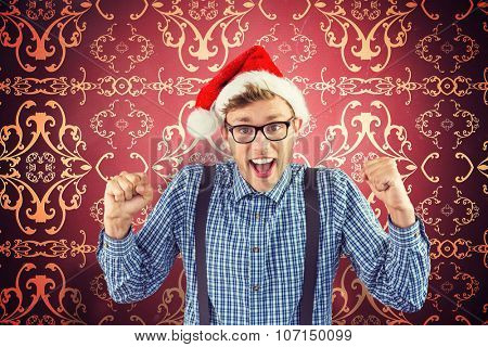Geeky hipster wearing santa hat against elegant patterned wallpaper in red and gold