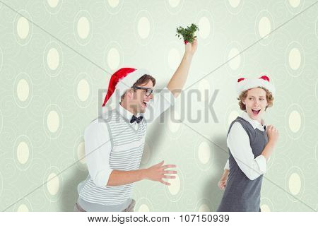 Geeky hipster running away from a man with mistletoe against blue and cream patterned wallpaper
