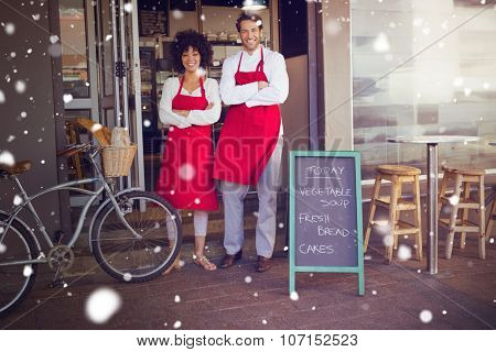 Snow against smiling colleagues in red apron with arms crossed