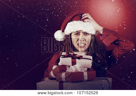 Festive stressed redhead holding gifts against snow
