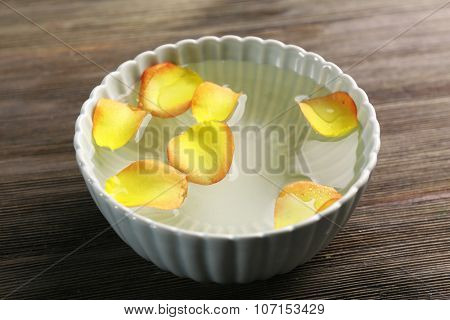 Yellow rose petals in a bowl of water on wooden background