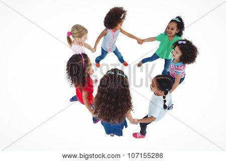 Smiling girls all holding each others hands against a white background