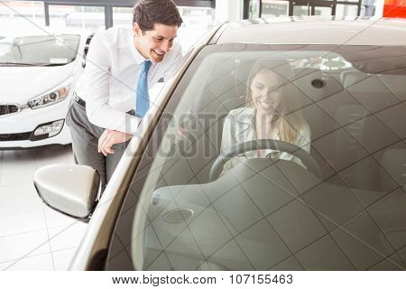 Businessman leaning on door showing car to customer at car showroom