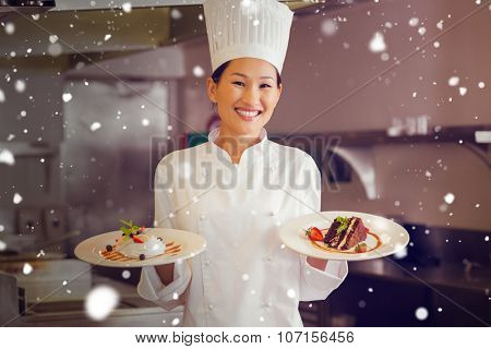 Snow against confident female chef holding cooked food in kitchen