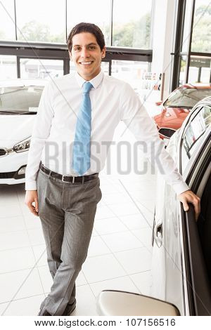 Man leaning on the door at new car showroom