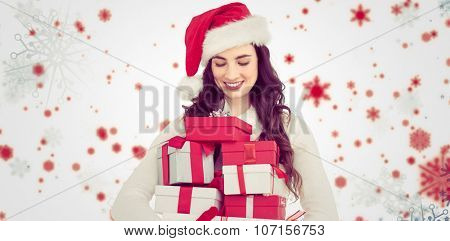 Festive brunette holding pile of gifts against snowflake pattern