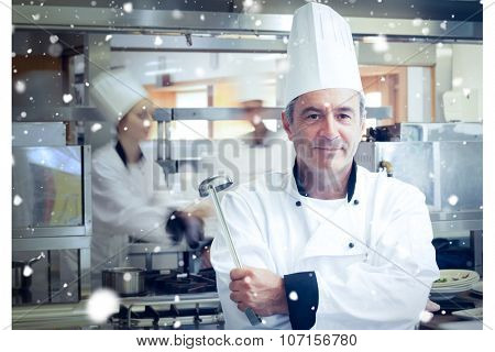 Snow against chef holding ladle