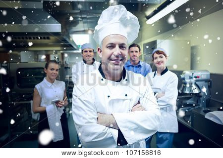 Snow against head chef posing with team behind him