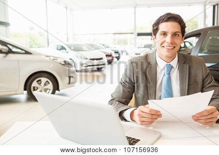 Smiling salesman reading a document at new car showroom