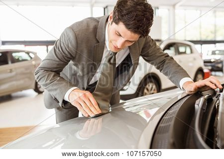 Focused businessman looking at the car body at new car showroom