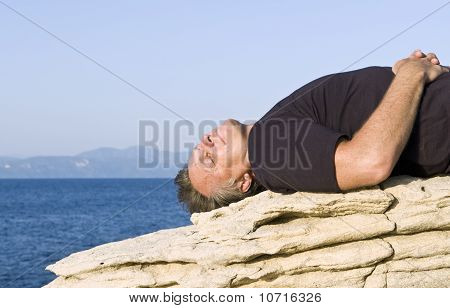 A man laying on a rock and relaxing in the sun.