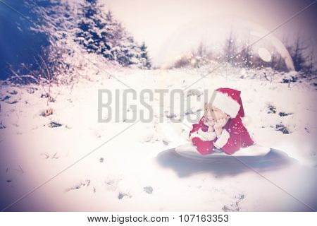Festive child in snow globe against snow covered landscape
