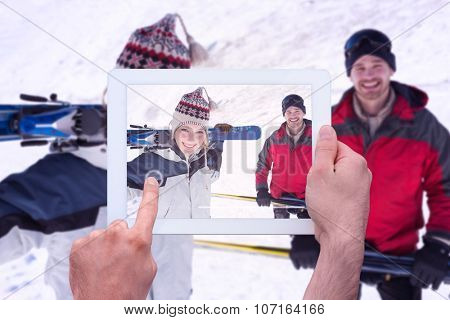 Hand holding tablet pc against portrait of a smiling couple with ski boards on snow