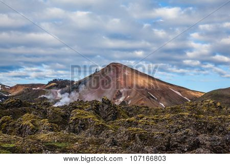 In the hollows of the mountains from the ground rises steam. Picturesque rhyolite mountains surround the valley. Summer morning in the National Park Landmannalaugar, Iceland