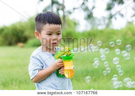 Thrilled little boy play with bubble gun