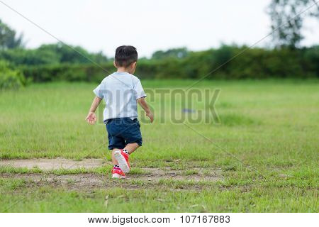 The back view of the little boy walking on the grassland