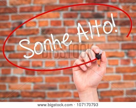 an Hand writing Sonhe Alto! (Dream Big in Portuguese) with black marker on visual screen.