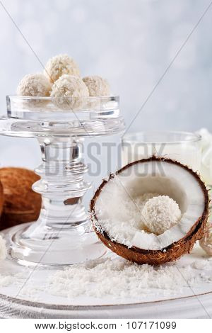 Candies in coconut flakes and fresh coconut on color wooden table, on light background