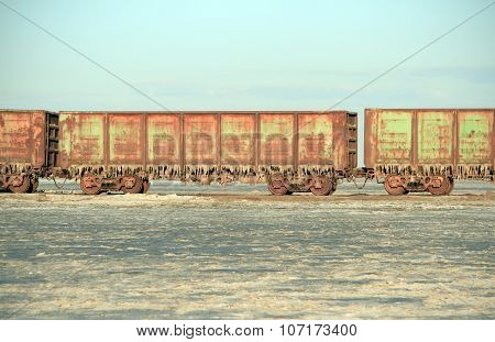 Old rusty train cars with stalactites of salt