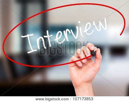 Man Hand writing Interview with black marker on visual screen.