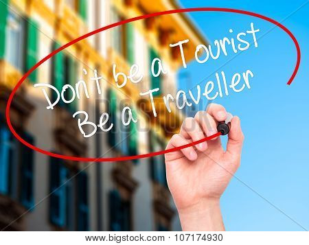 Man Hand writing Don't be a Tourist Be a Traveller with black marker on visual screen.