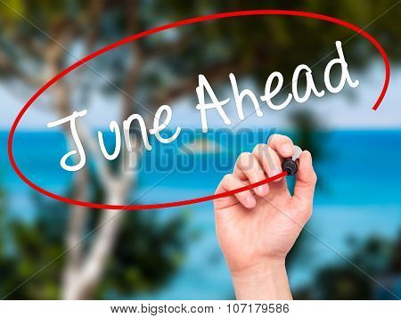 Man Hand writing June Ahead with black marker on visual screen.