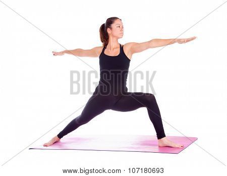 Beautiful woman doing Virabhadrasana 2 pose on yoga class, Studio shot.