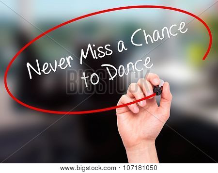Man Hand writing Never Miss a Chance to Dance with black marker on visual screen.