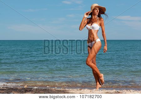 Young attractive girl enjoys hot summer day at the beach.