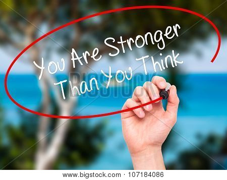 Man Hand writing You Are Stronger Than You Think with black marker on visual screen.