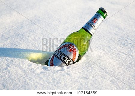 MONTREAL, CANADA -21 January 2015: A bottle of Beck's beer cools in the winter snow. Beck's is the bestselling German beer in the world. In Montreal, january 2015
