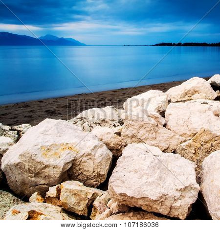 Cold And Cloudy Dany On The Sand Beach With Rocks In Front In Southern Croatia