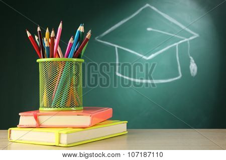 Metal cap of crayons with stack of books and bachelor hat drawing on blackboard background