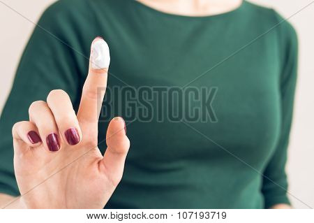 Woman In A Green T-shirt And A Maroon Manicure Shows Hand Cream On Finger