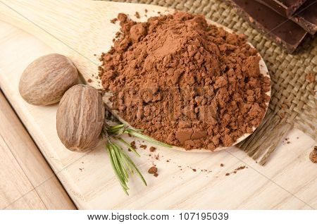 Nutmeg With A Sprig Of Rosemary And Cacao Powder In The Wooden Spoon On Wooden Table