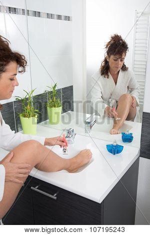 Close Up Of Woman Shaving Legs