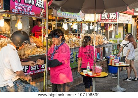 Shoppers walking past seafood vendor at Tamsui riverside shopping area