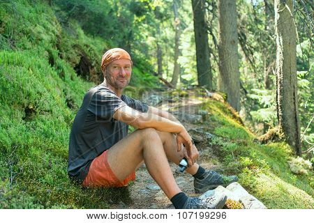 Happy Hiker Man Is Resting, Sitting On The Route With Gps Receiver In Hand, Smiling And Looking At T