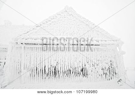 Snow And Ice Covered House After Blizzard At Winter