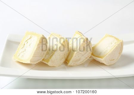 plate of sliced soft white rind cheese
